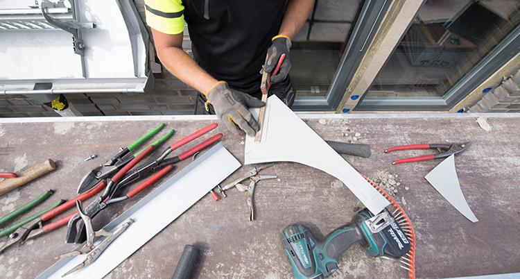 Eb person klädd i arbetskläder jobbar med plåt på et bord, där det ligger verktyg.