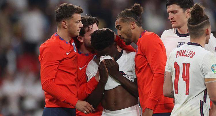 Englands spelare Bukayo Saka tröstas av sina lagkamrater efter att han missat sin straff.