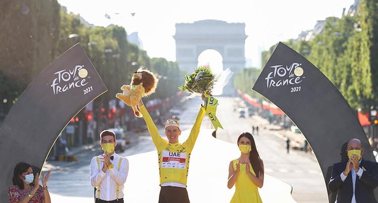 I mitten står en man med gul cykeltröja. Han sträcker armarna mot luften och håller i en pokal och en blombukett. Han flankeras av flera personer. De står utomhus, på en stor karta i Paris. Triumfbågen syns i bakgrunden.