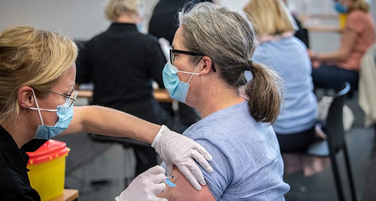 En kvinna får vaccination i armen av en annan kvinna.