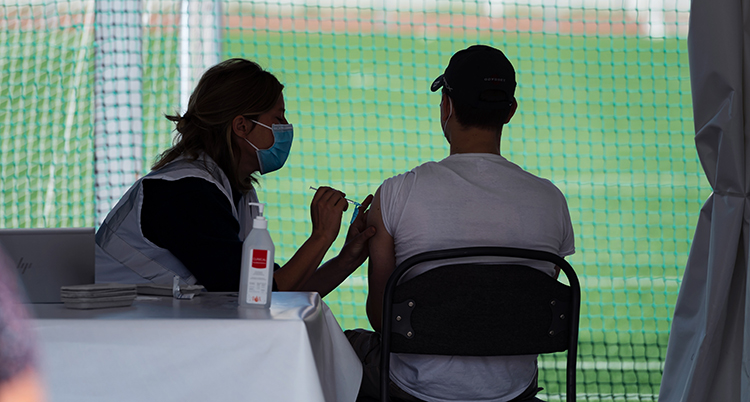 De är intill en fotbollsplan. Hon ger honom en spruta i armen. Han sitter med ryggen mot kameran. Han har t-shirt och keps.