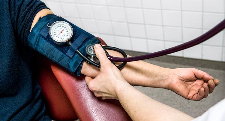 Sjuksköterska mäter en kvinnas blodtryck.