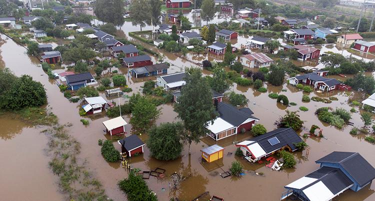 En bild tagen från luften över ett område med hus. Marken syns inte utan där är brunt vatten mellan husen.