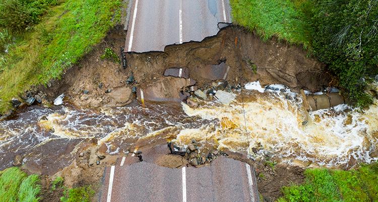 en bild tagen ovanifrån på en väg som rasat. Vägen är delad rakt av, i ravinen mellan vägdelarna forsar vatten.