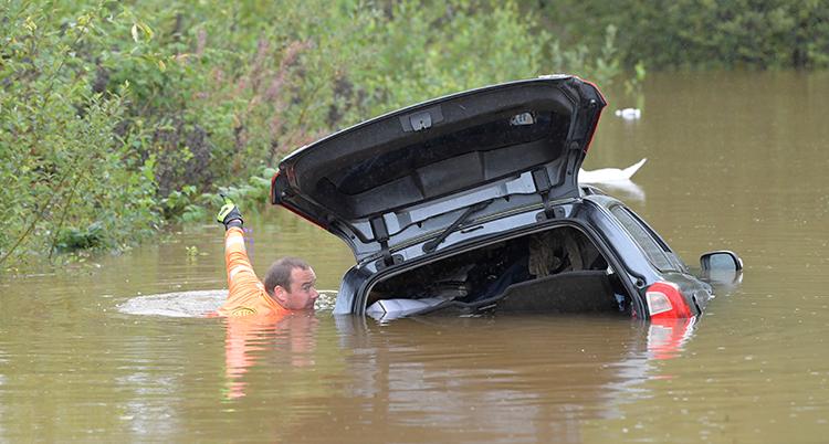 En man står vid sin bil som är nästan helt översvämmad. Vi ser bara taket på bilen och en del av bakluckan som är öppen. Mannen står bredvid i djupt vatten upp till axlarna och håller i sig i den öppnade bakluckan.