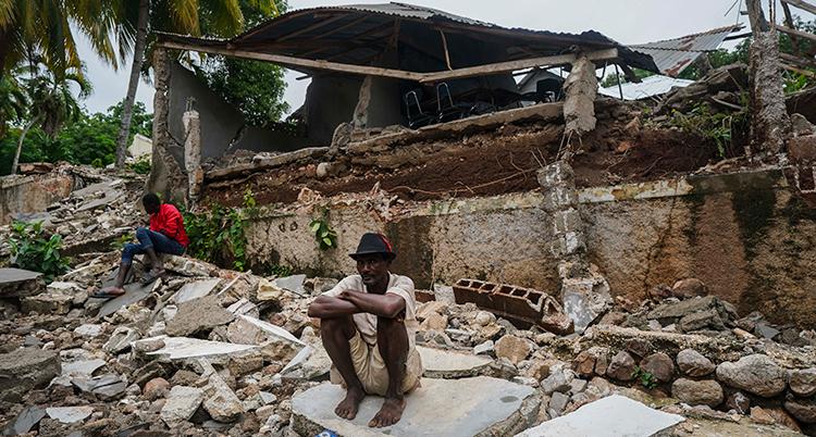 en man sitter framför bråte från ett rasat hus.
