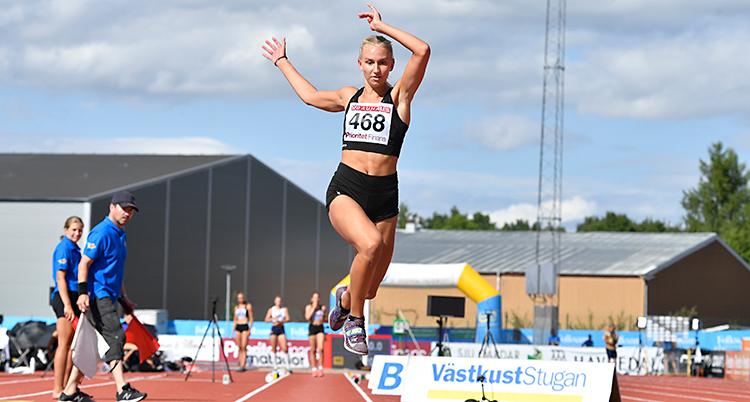 Maja Åskag är mitt i ett hopp. Hon är i luften. Hon tävlar i en svart dräkt.