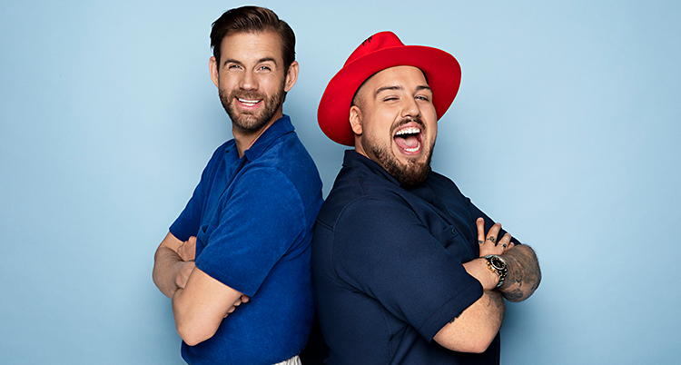 Pär och Anis står med ryggarna mot varandra. De ler och tittar in i kameran. Båda har blå tröjor. Anis har en röd hatt på sig.