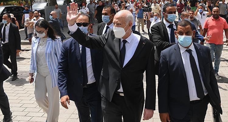 Presidenten går på en gata. Han har vakter med sig. Han vinkar till människor.