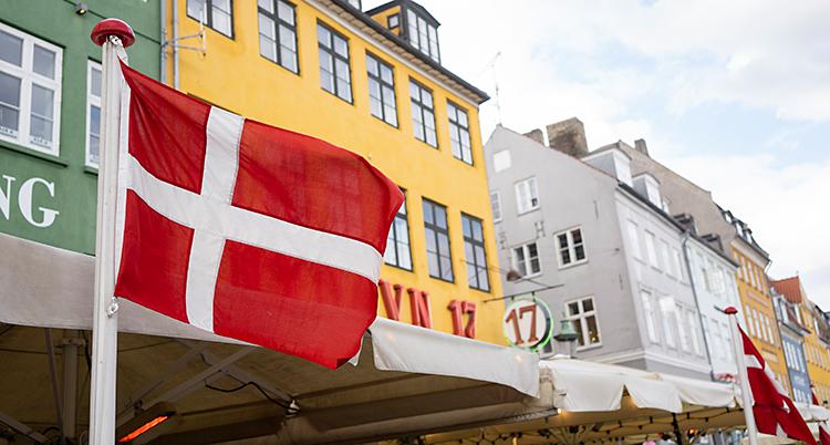 Bilden visar hus i området Nyhavn i Köpenhamn. Framför husen finns det uteserveringar och danska flaggor.