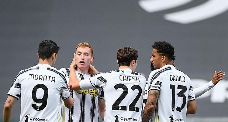 Från en match i fotboll. Dejan Kulusevski har gjort mål. Han blir kramad av sina lagkamrater. De har tröjor som är vita och svarta.