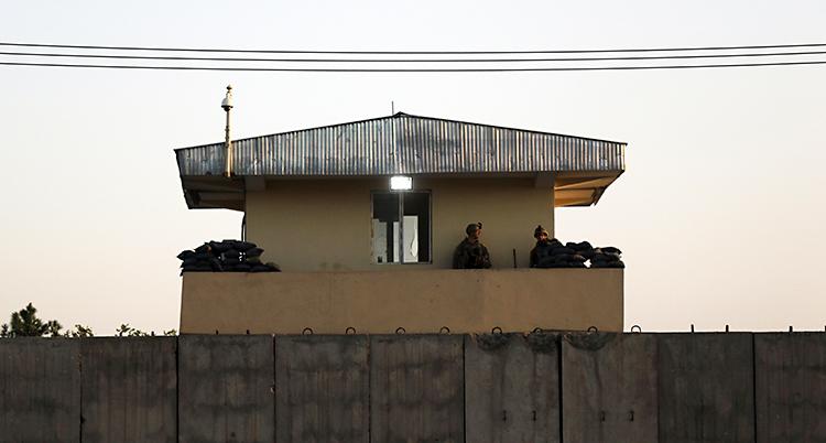 En mur. Bakom muren finns ett hus. Där står soldater och vaktar.