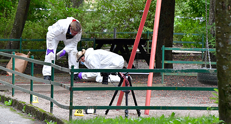 Bilden är tagen utomhus vid en lekplats. Två tekniker från poliserna jobbar med att leta spår. De har på sig vita overaller.