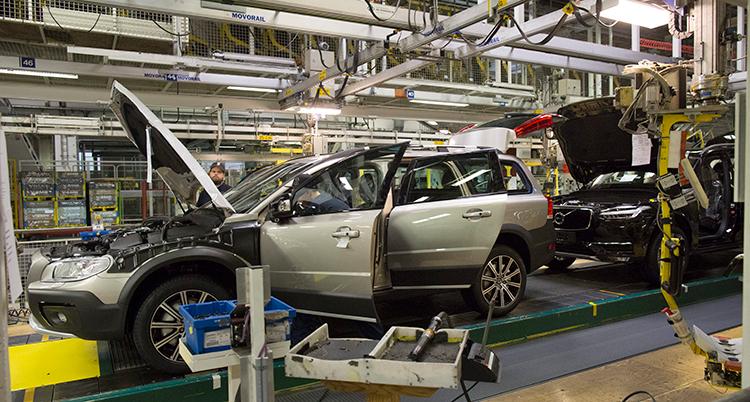 En bil blir tillverkad i en fabrik. Den står på ett band och har motorhuven uppfälld.