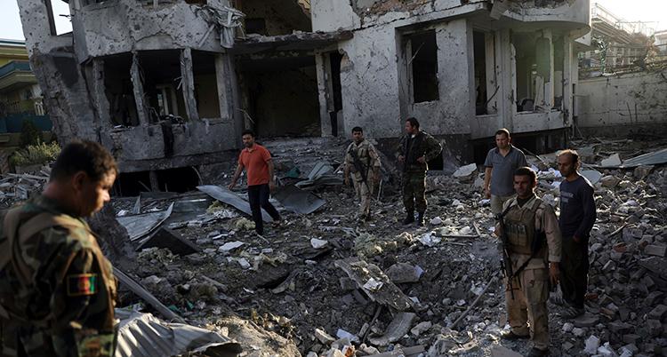 Ruiner av ett bombat hus syns bakom män som står på marken, som är full av trasiga saker.