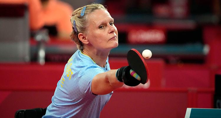 Hon har ljusblå tröja, ljust hår, och är på väg att slå en vit bordtennisboll med racket hon håller i höger hand.