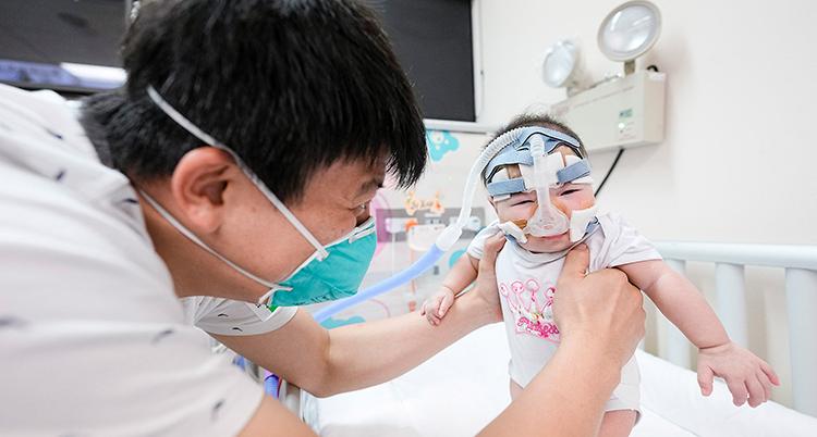 Han har mörkt hår och munskydd, han håller i en baby som har en mask över ansiktet. De är på ett sjukhus.