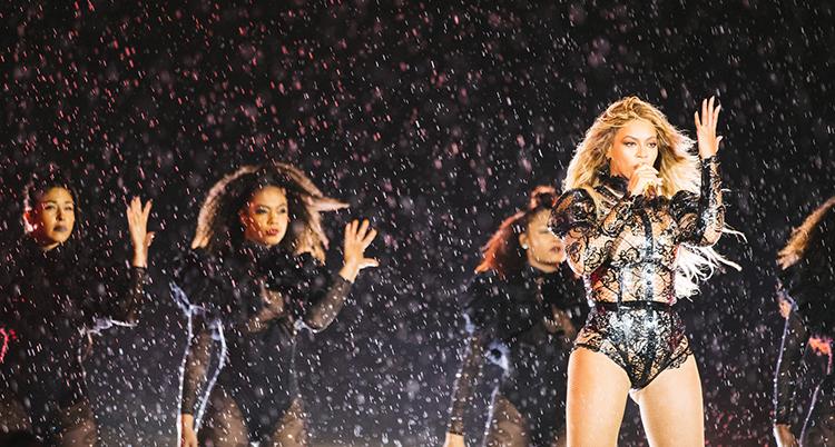 Hon står längst fram, hon har stort, böljande hår, svart scendräkt av spets och håller i en mikrofon. Hon håller upp andra handen vid huvudet. Bakom står kvinnor i svarta scendräkter. Scenen är mörk.