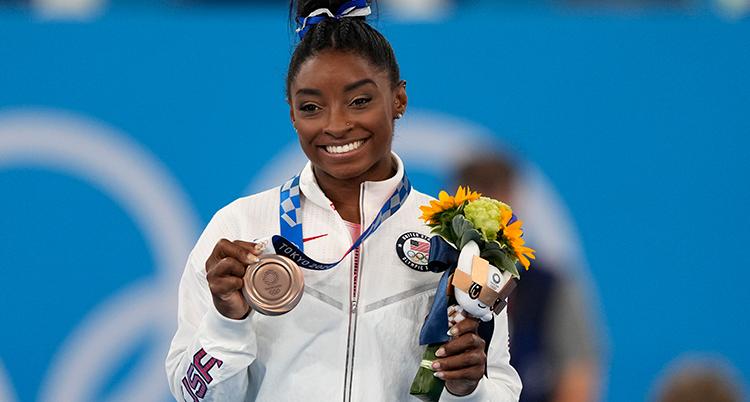 Hon har vit jacka, håret i en tofs, hon ler och håller upp medaljen som hon har runt halsen. Hon håller en blombukett i andra handen.