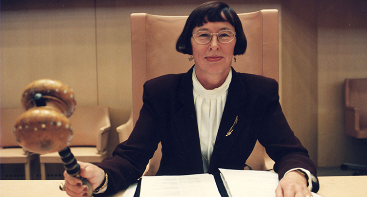 Hon har mörkt hår, glasögon, vit blus och kavaj. Hon håller i en ordförandeklubba.