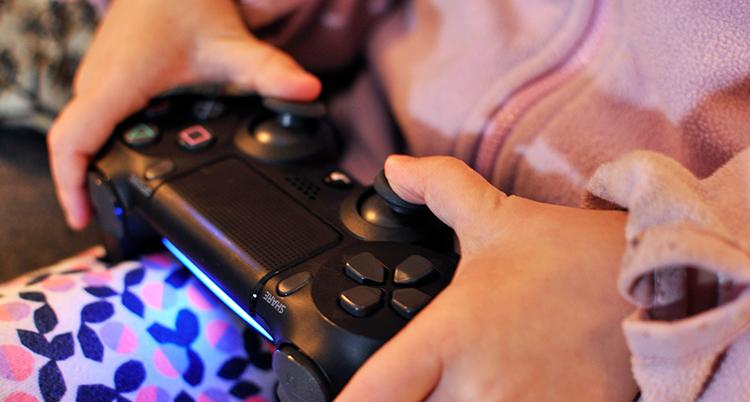 barnhänder håller i en spelkontroll