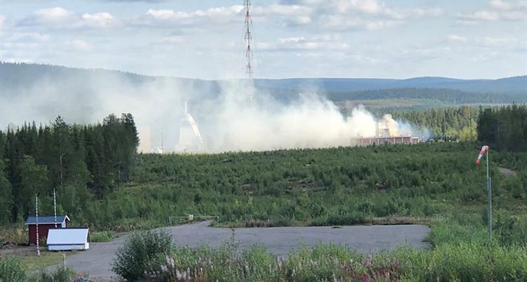 Rök syns över skog i en fjällmiljö. I förgrunden syns en asfalterad platta och en röd bod.
