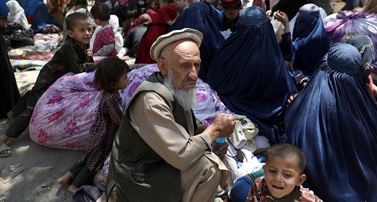 En äldre man sitter ner. Framför honom sutter ett barn som gråter. Bakom dem finns många människor som sitter ner.