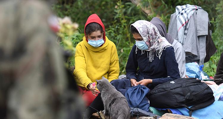 Två kvinnor sitter på marken. De bär munskydd.