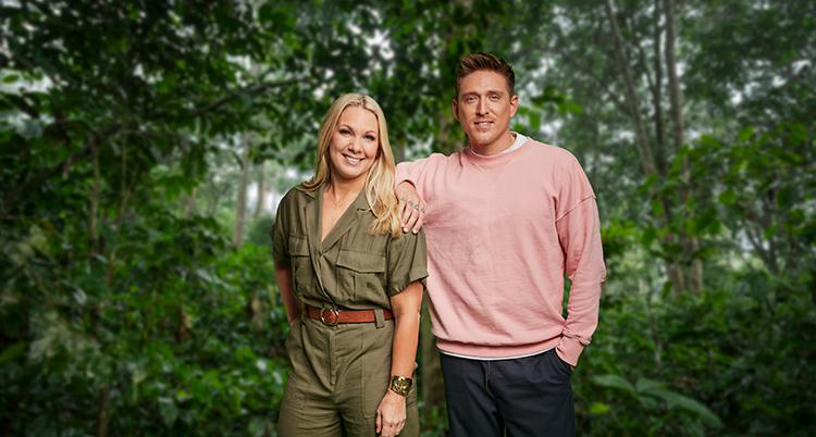 Han har rosa tröja och håller ena armen på hennes axel. Hon har bruna kläder. De står intill varandra och tittar in i kameran. Bakom syns grön regnskog.