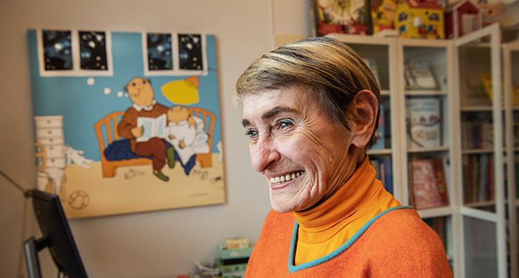 Hon ler och har en orange tröja. Bakom henne syns en tavla med Alfons och hans pappa.