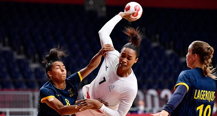 En fransk spelare i vit dräkt hoppar och skjuter. En svensk spelare har tag i hennes arm och försöker stoppa henne.