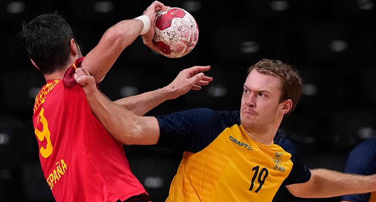 En spansk spelare har bollen och försöker att skjuta. En svenska hålleri hans tröja för att stoppa honom.