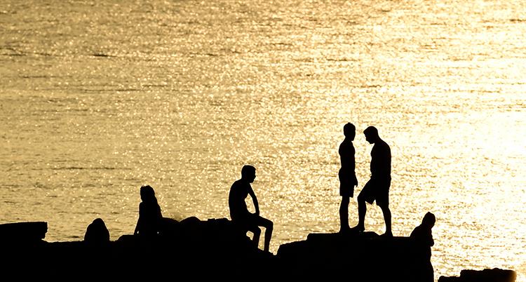 Människor på en klippa vid havet. Solen lyser bakom dem och de syns bara som svarta siluetter.