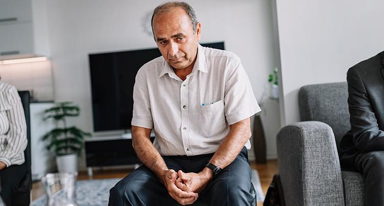 Mannen ser sorgsen ut. Mannen har ljus kortärmad skjorta, tunt hår, han sitter på en stol i ett rum, med händerna knäppta i knät.