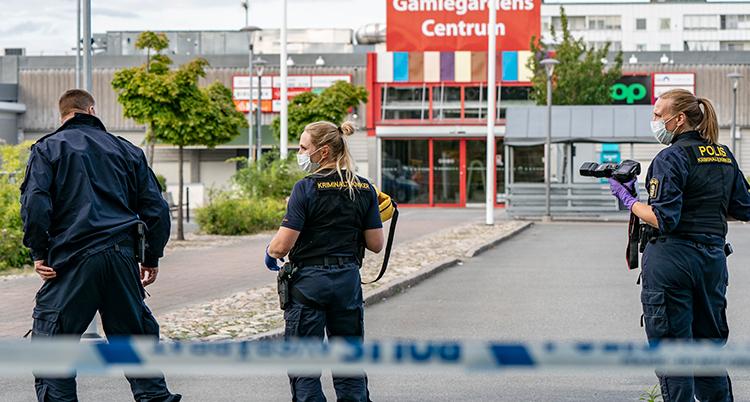 Tre poliser står med ryggen mot kameran. Bakom dem är ingången till köpcentret.