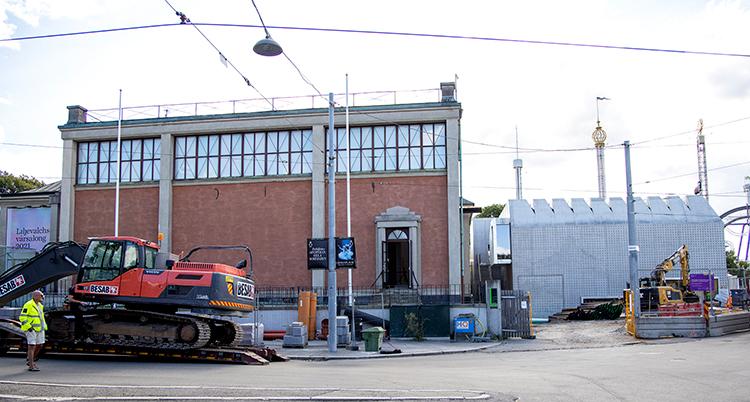En byggnad i brunt tegel syns till vänster och till höger om den en byggnad i ljus betong. I förgrunden syns en grävmaskin.