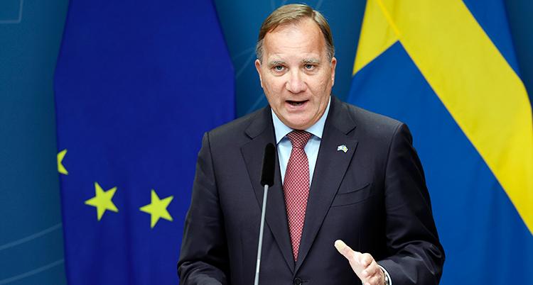 Löfven talar och gör en rörelse med handen. Svenska flaggan är bakom honom.