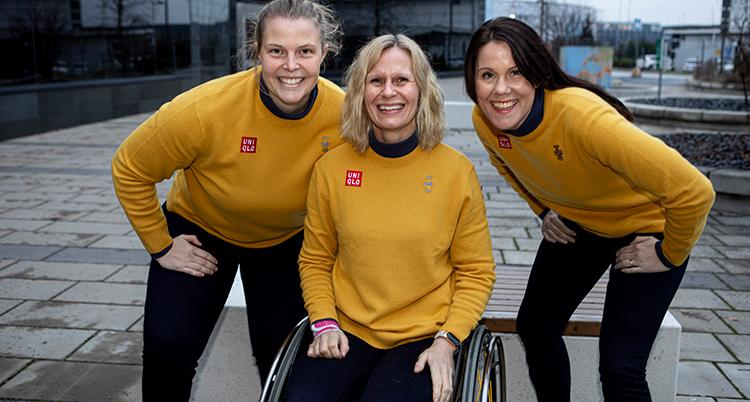 De har gula tröjor, de står utomhus och ler. Kvinnan i mitten sitter i en rullstol, de andra två hukar sig ner intill.