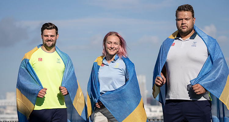 De tre medaljörerna står bredvid varandra. Alla har en svensk flagga över axlarna. Sarah Sjöström står i mitten.