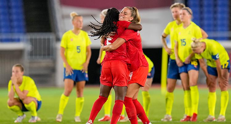 Två fotbollsspelare i röda kläder kramar varandra, besvikna spelare i gult syns bakom.