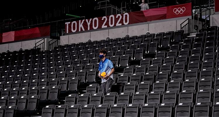 En man på en helt rom läktare. Bakom dom är en skylt där det står Tokyo 2020.