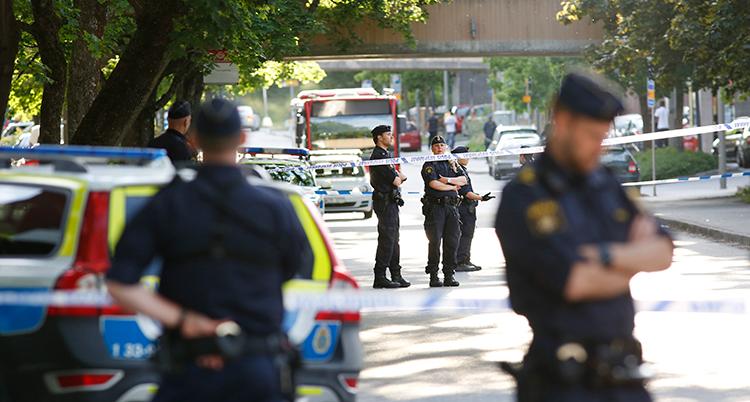 Flera poliser står på en gata. De har spärrat av med tejp.