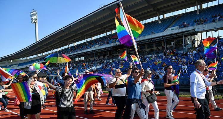 Människor går in på en idrottsarena med prideflaggor i händerna.