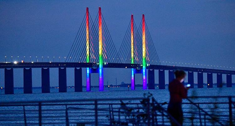 En lång bro över vattnet. På mitten av bron är pylonerna upplysta i regnbågens färger.