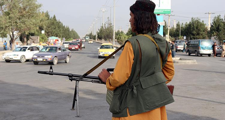 en taliban står på en trafikerad gata och håller i ett gevär.