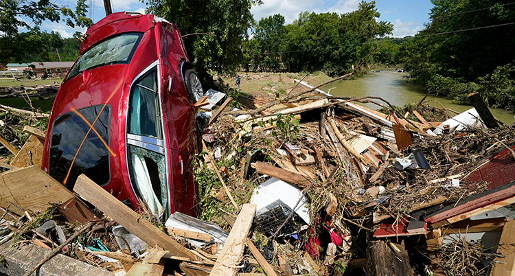 En bil stor rakt upp i massorna med bråte intill en flod.