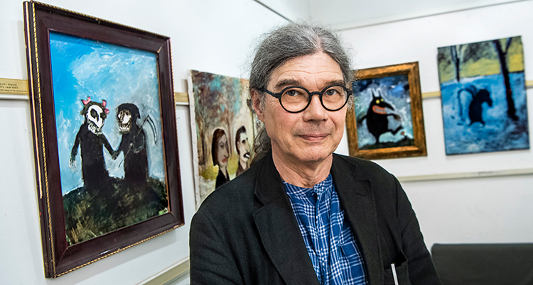 Han har grått hår i en tofs, svartabågade glasögon, han tittar in i kameran och bakom hänger målningar.