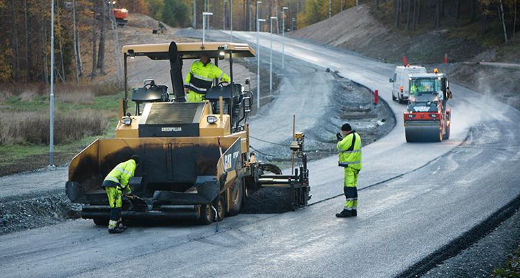 En stor maskin på en väg. Bredvid dem står två personer i gula kläder. De håller på att lägga asfalt på en väg.