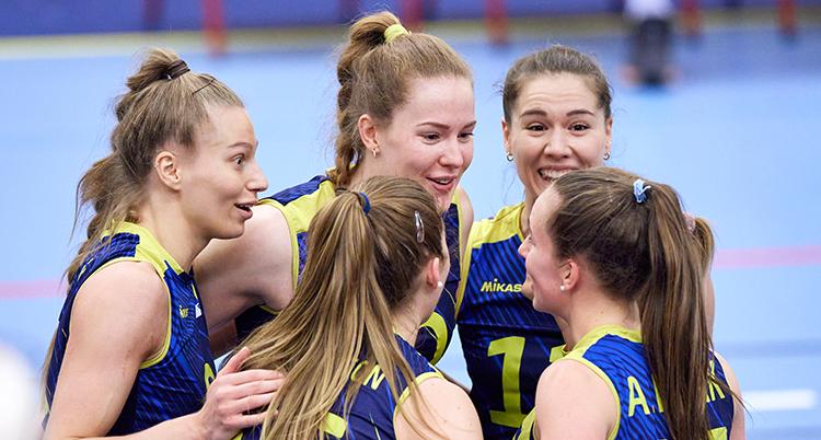 Fem kvinnor i blå träningslinnen står i en cirkel på planen och klappar om varandra