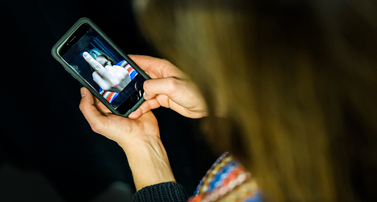 """En kvinna tittar på en bild på sin mobil. Bilden visar en person som gör """"fula fingret"""" mot kvinnan."""
